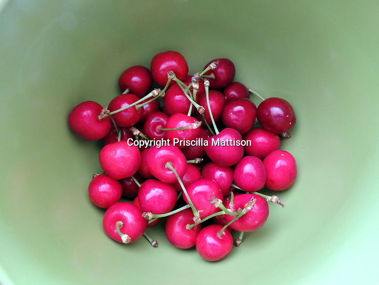Red cherries seem to approach from a green background.