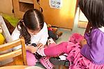 Education Preschool 3-4 year olds girl helping to tie classmate's shoe