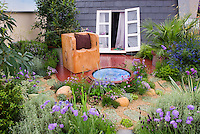 Garden and small water feature with rustic chair on roof of house, whith window and house evident