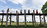 18 JUNE 2015, Mandalay, Myanmar:  Monks cross the U Bein Bridge; a crossing that spans the Taungthaman Lake near Amarapura in Myanmar. The 1.2-kilometre bridge was built around 1850 and is believed to be the oldest and longest teakwood bridge in the world. <br /> The bridge was built from wood reclaimed from the former royal palace in Inwa. It features 1,086 pillars that stretch out of the water, some of which have been replaced with concrete. Though the bridge largely remains intact, there are fears that an increasing number of the pillars are becoming dangerously decayed. Some have become entirely detached from their bases and only remain in place because of the lateral bars holding them together. Picture Graham Crouch/The Australian Magazine