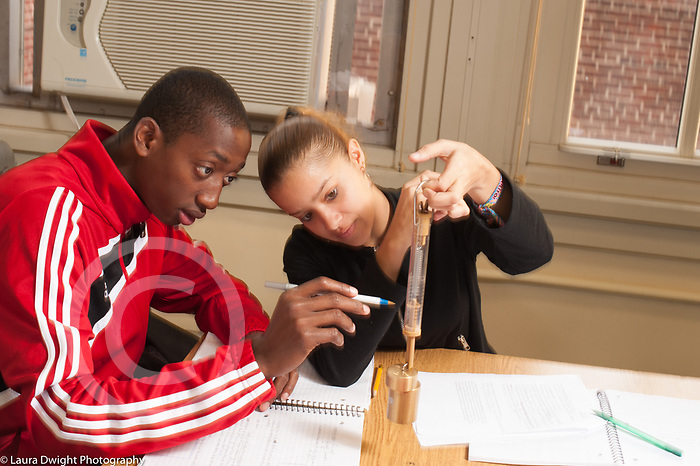 Education High School science class male and female students working together on experiment