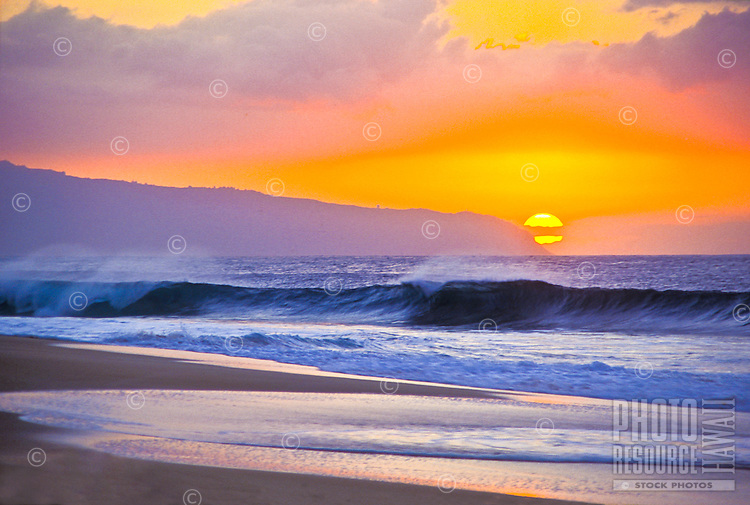 The sun sets over big waves at Sunset Beach, North Shore, Oahu