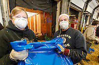 Getting ready for Iditarod 2016, two lady volunteers hold a bag of straw as  others  zip-tie, stack and shrinkwrap pallets of straw and hay on Thursday, February 11, 2016 at Airland Transport in Anchorage.  Nearly 1700 bales will be sent out to over 20 checkpoints along the trail. Iditarod 2016