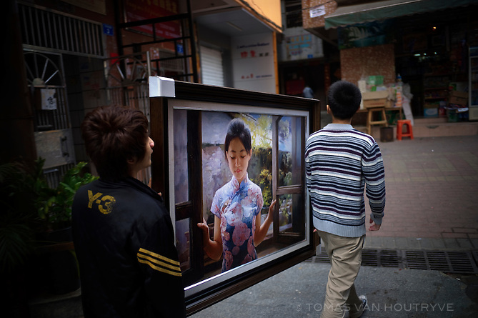 Men carry a painting in the Dafen area of Shenzhen, China on Feb. 6 2012. In addition to original art works, Dafen produces thousands of inexpensive reproductions which are sold to hotels around the world.