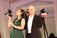 """VENICE, ITALY - SEPTEMBER 11: Laure Calamy and Director Eric Gravel pose with the Orizzonti Awards for Best Actress and Best Director for """"A Plein Temps"""" (Full Time) at the awards winner photocallduring the 78th Venice International Film Festival on September 11, 2021 in Venice, Italy."""
