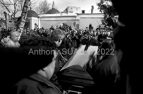 Moscow, Russia .1995.the coffin of Vladislav Listyev, the famous Russian television host who was gunned down in his aptarment is lowered into the ground under the eyes fo the media and massive crowds. His killing was business related.