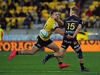 Chiefs Damian McKenzie reverse passes under pressure from Hurricanes Wes Goosen during the Super Rugby Aotearoa match between the Hurricanes and Chiefs at Sky Stadium in Wellington, New Zealand on Saturday, 8 August 2020. Photo: Dave Lintott / lintottphoto.co.nz