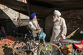 Amritsar, Punjab, India. Two Sikhs talking at the market with bicycle and motorbike.