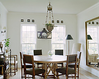Antique pieces blend seamlessly with a brand new circular dining table in Victoria Hagan's Montauk retreat. A large mirror elongates the space, creating a myriad of new angles.