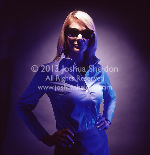 Dramatically lit photograph of blond woman with dark sunglasses<br />