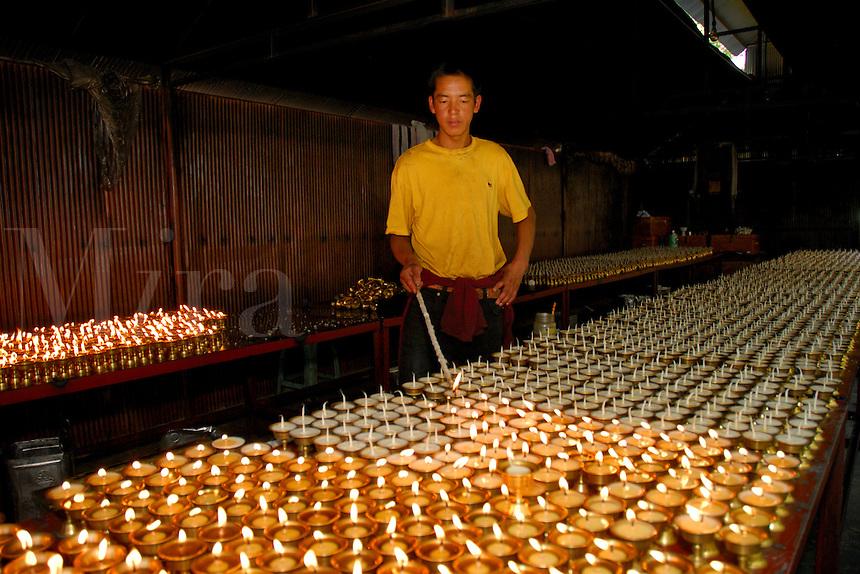 Lighting yak butter lamps at Palha Lupuk cave temple, Lhasa, Tibet, China.