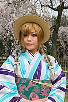 Japan, Kyoto. Japan, Kyoto. Woman in striped kimonos enjoyin the cherry blossoms in Kyoto Gyoen National Garden. Model released