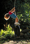 young boy swinging on tire-swing
