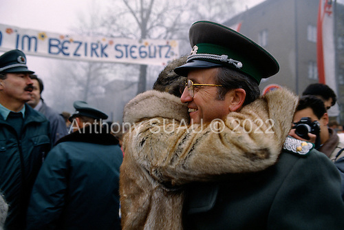 Lichterfelde, Berlin (West) and Teltow, Potsdam (East) crossing post, Germany<br /> November 14, 1989 <br /> <br /> An East German woman embraces a guard after crossing the border near the Berlin Wall. Germans gathered as the wall is dismantled and the East German government lifts travel and emigration restrictions to the West on November 9, 1989.