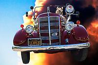 A dog pilots an antique fire engine through a cloud-scattered sky.