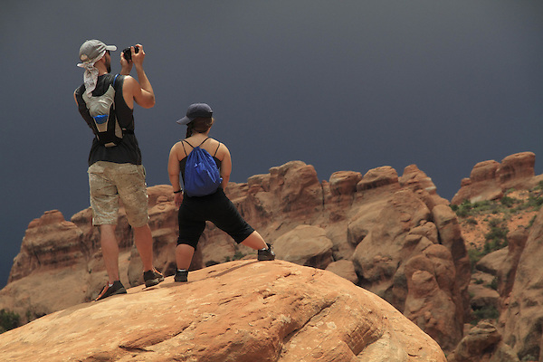 Small Caucasian woman with friend in Arches National Park, Moab, Utah, USA. .  John offers private photo tours in Arches National Park and throughout Utah and Colorado. Year-round.