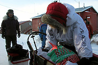 Paul Gebhardt packs dog food in his sled before blowing through Koyuk. Photo by Jon Little.