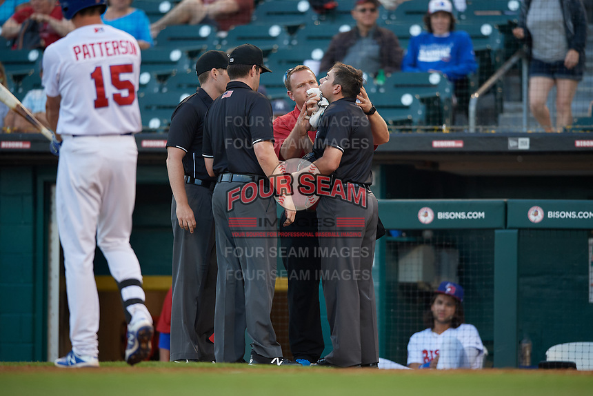 Buffalo Bisons trainer Bob Tarpey tends to home plate umpire Mike Wiseman after an injury as field umpires Richard Riley and John Bacon look on during an International League game between the Syracuse Mets and Buffalo Bisons on June 29, 2019 at Sahlen Field in Buffalo, New York.  Buffalo defeated Syracuse 9-3.  (Mike Janes/Four Seam Images)