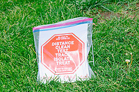 """A flyer listing ways to fight the coronavirus pandemic is seen in a ziploc bag on the grass as people gather for an anti-lockdown protest organized by the alt-right group Super Happy Fun America near the home of Massachusetts governor Charlie Baker in Swampscott, Massachusetts, on Sat., May 16, 2020. The protest was in defiance of Massachusetts orders mandating face coverings and social distancing and prohibiting gatherings larger than 10 people during the ongoing Coronavirus (COVID-19) global pandemic. The state's stay-at-home order is expected to be updated on May 18, 2020, with a phased reopening plan issued by the governor as COVID-19 cases continue to decrease. Anti-lockdown protests such as this have become a conservative cause and have been celebrated by US president Donald Trump. Many of the protestors displayed pro-Trump messages or wore Trump campaign hats and shirts with phrases including """"Trump 2020"""" and """"Keep America Great."""" Super Happy Fun America, organizers of the protest, are an alt-right organization best known for creating the 2019 Boston Straight Pride Parade."""