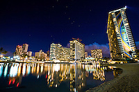 Waikiki and Ala Moana hotels at night with lights reflected in a lagoon on Oahu