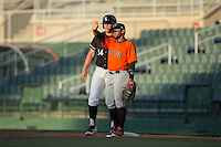 Augusta GreenJackets first baseman Miguel Gomez (9) shields his eyes from the sun while keeping an eye on Corey Zangari (14) of the Kannapolis Intimidators at Intimidators Stadium on May 30, 2016 in Kannapolis, North Carolina.  The GreenJackets defeated the Intimidators 5-3.  (Brian Westerholt/Four Seam Images)