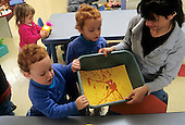 MR / Schenectady, New York. Schenectady Day Nursery (private nonprofit daycare center in urban area). Toddler classroom..Teaching aide (Chinese-American and Caucasian) does art project using marbles rolled in paint with students (Twin girls; Age 2). MR: Rob5, Rob6, Hoy1. © Ellen B. Senisi