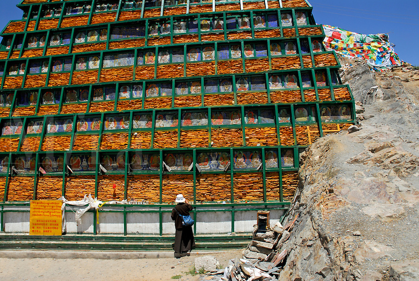 Buddhist pilgrim at reinforced mound of stone tablets and old painted carvings on the Lingkhor pilgrim circuit as it ascends Chagpo Ri mountain, Lhasa, Tibet, China.