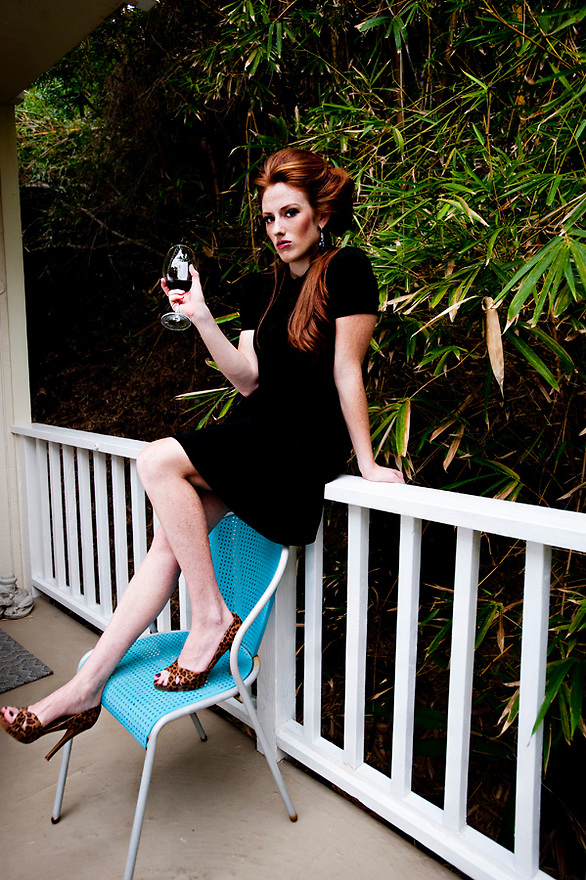 Red head taking a break drinking wine on teal chair.  Thrift store fashion finds.  Little Black Dress by Liisa Roberts Photography.