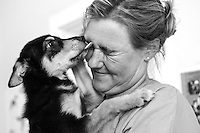 Veterinarian, Saskia Karius, gets a lick from a severely wounded puppy at IFAW's CLAW clinic on the grounds of the Durban Deep mine close to Soweto in South Africa. This program provides veterinary services to cats and dogs in some of the poorest shantytowns outside of Johannesburg, South Africa. 2/21/12 Julia Cumes/IFAW