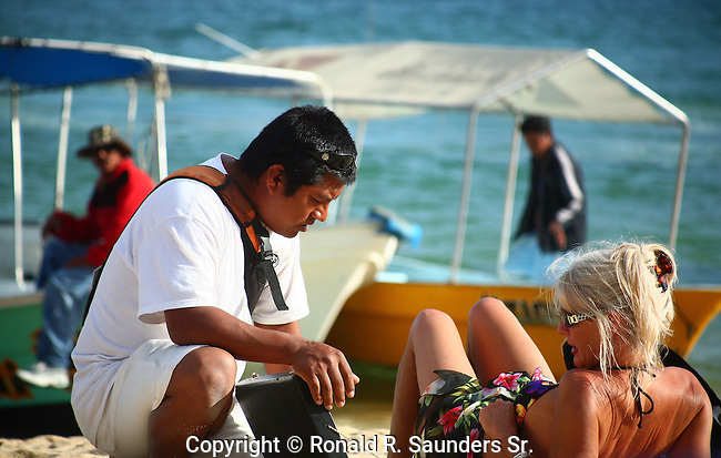 SUNBATHER AND MEXICAN BEACH VENDOR IN CABO SAN LUCAS