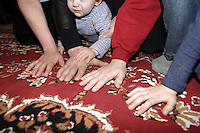 A Chechen man with is Family (From the left: the wife hand, the husband hand with the young baby hand on the top and the two elder brother hands ).  .They have suffer violence from the Russian army and from the FSB (Ex KGB). There life was in danger, so they escape to Inguchia and them pay 1200.-Euro per person, to reach illegally Switzerland via Germany..They pass the first interview in a CERA centre and are now waiting, in a apartment of the FAREAS in the cantonal centre of Moudon, to pass a second interview to be accept as refugee in Switzerland.