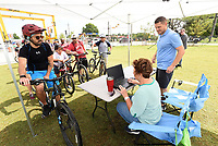 RIDE 'ROUND RAILYARD LOOP<br />Edgar Duarte (left) of Bentonville checks his biking group in on Saturday July 17 2021 for a ride during the Rogers Bike Festival headquartered at Railyard Park in downtown Rogers. Ross Phillips (right) with the Rogers Lowell Area Chamber of Commerce helps check in riders. The festival featured road-bike rides on the 15-mile Raillyard Loop that circles the city and mountain bike rides at Lake Atalanta Park east of downtown. Vendors set up tents to show their wares near Railyard Park's Butterfield Stage, where a concert by The Uncrowned Kings took place after the riding was through. Go to nwaonline.com/210718Daily/ to see more photos.<br />(NWA Democrat-Gazette/Flip Putthoff)