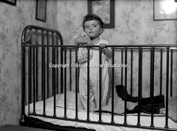 Product: Antique Brass Crib<br /> <br /> Wilkinsburg PA:  Helen Stewart getting ready for bed in her new brass crib.