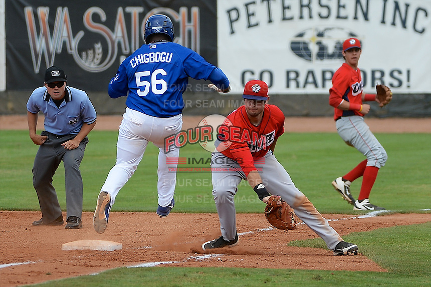 Justin Chigbogu (56) of the Ogden Raptors beats the throw against the Orem Owlz as Owlz first baseman Eric Aguilera (33) fields the ball at Lindquist Field on July 07, 2013 in Ogden Utah. (Stephen Smith/Four Seam Images)