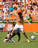 Houston Dynamo forward Brian Ching (25) attempts to stay on his feet after a tackle by Los Angeles Galaxy defender Gregg Berhalter (16). Houston Dynamo tied Los Angeles Galaxy 0-0 at Robertson Stadium in Houston, TX on October 18, 2009.