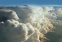 High aerial view of massive cumulus cloud formations forming an abrupt textured slope