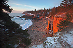 A rock spire soaks up the direct light during a winter sunrise in Monument Cove at Acadia National Park, Maine, USA