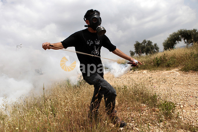 A masked Palestinian protester uses a slingshot to hurl back a tear gas canister fired by Israeli security forces during clashes following a demonstration marking Palestinian Prisoners' Day, in the West Bank village of Bilin, near Ramallah on April 17, 2015. Palestinian human rights groups say 6,000 Palestinian prisoners remain in Israeli prisons and detention camps. Photo by Shadi Hatem
