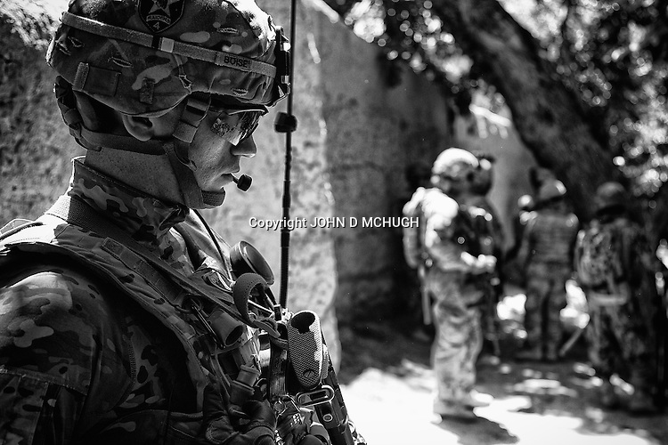 Captain Matthew Boise, Bayonet Company Commander, 1-38 Infantry, listens on his radio during a short lull in a five hour firefight with the Taliban in Pay-E Moluk village,  Panjwayi district, Kandahar, 30 April 2013. (John D McHugh)