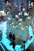 China. Shanghai. World Expo. Expo 2010 Shanghai China.  China Pavilion. A group of chinese tourists walk on an electric blue river, symbol of the Yellow River or Huang He / Hwang Ho inside the Ningxia pavilion. A tower with video scren present the various people living in Ningxia, among them the Hui, one of the officially recognized Nationalities of China. 25.06.10 © 2010 Didier Ruef