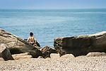 Hammonasset Beach State Park, Madison, CT. Woman among rocks. Long Island Sound.