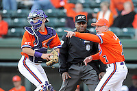 Head coach Jack Leggett of the Clemson Tigers motions to catcher Chris Okey (25) that a runner is advancing as Okay was challenging a close call at the plate in the Reedy River Rivalry game against the South Carolina Gamecocks on March 1, 2014, at Fluor Field at the West End in Greenville, South Carolina. South Carolina won, 10-2. (Tom Priddy/Four Seam Images)