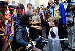 Notting Hill annual carnival 1979, black British man dancing with young white girl. Ethic harmony, group of people watching. 1970s