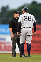 Staten Island Yankees manager Mario Garza (28) argues a call with field umpire Chris Scott during a game against the Batavia Muckdogs on August 7, 2014 at Dwyer Stadium in Batavia, New York.  Staten Island defeated Batavia 2-1.  (Mike Janes/Four Seam Images)