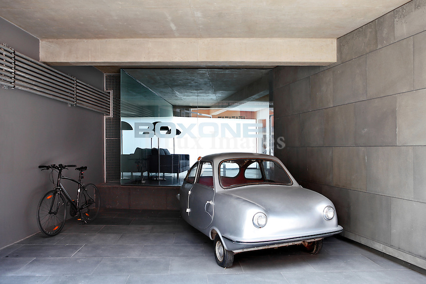 silver car in the garage..In the ground floor of Boxone - a residential complex of sixteen lofts is the house of photographer Haris Christopoulos. Located in the Gazi area of downtown Athens his modern loft was built by the architect Thanasis Kaloyiannis.
