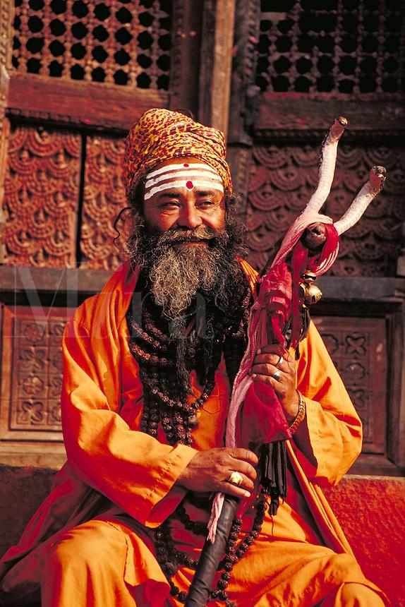 Holy man in saffron robe seated on steps of Shiva-Parvati Temple holds his staff. Kathmandu, Nepal.