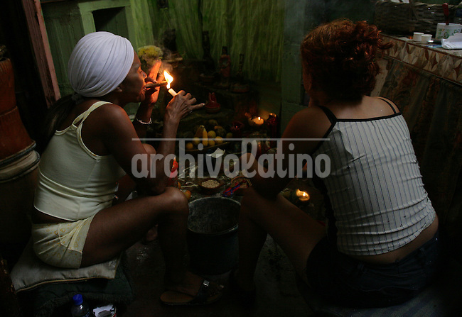 A priestess called Luisa smokes a cigar infront the image of Queen Maria Lionza before a healing ceremony  at her home near Sorte Mountain in yaracuy, the center of popular religions in Venezuela.