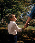 young boy 8 year old holding hand and looking up to his father for guidance