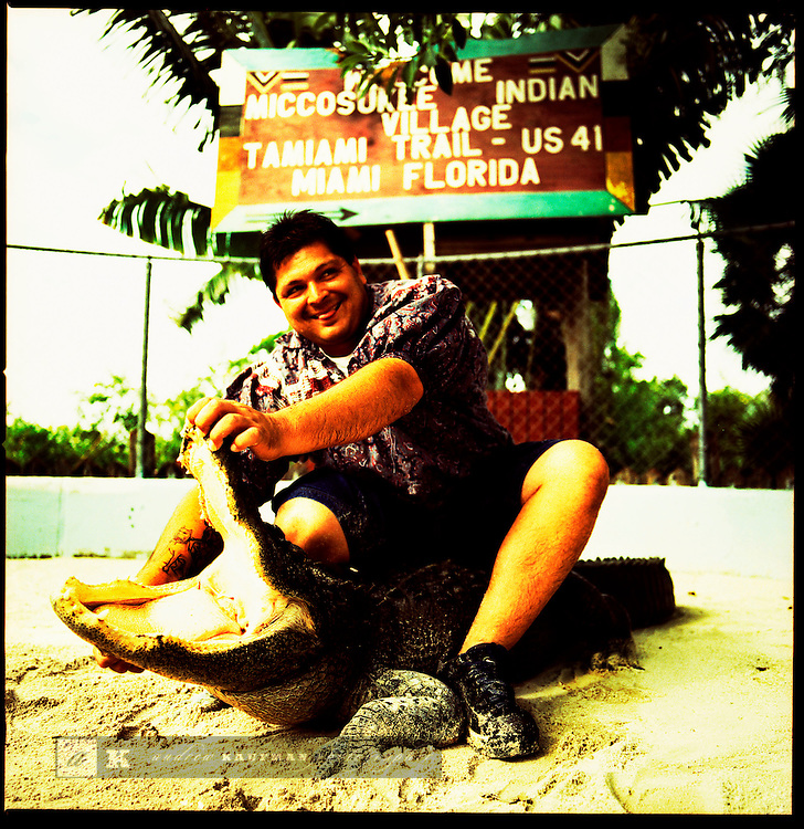 Kenny Cypress an American Indian holds open the mouth of an alligator, Miccosukee Tribe, Florida.