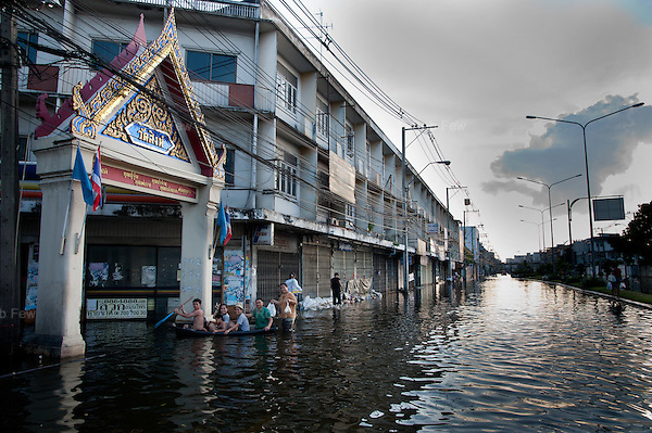 Local residents paddle towards a temple in western Bangkok.<br /> <br /> Thailand's worst floods for 50 years finally reached the suburbs of Bangkok in October 2011. While the government dithered and argued with itself, more than 200 people died.